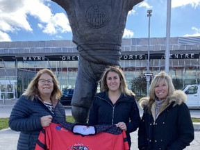 Brantford Girls Hockey Association registrar Cathy Drinkwater (left) holds an Ice Cats jersey outside the Wayne Gretzky Sports Centre, along with Lexi Cross  and her mother, Leslie Cross. The BGHA has initiated three annual scholarships for its players, including one named in honour of longtime coach Brian Cross, who died Oct. 16. He is Lexi's father and Leslie's husband.