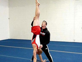 Former Canadian gymnast Alexander Jeltkov, now a coach at the Loyalist Gymnastics Club in Kingston, works with former senior level elite athlete and current coach Mattie Sergeant in a 2012 photo. Jeltkov was recently inducted into the Gymnastics Canada Hall of Fame. (Supplied Photo)