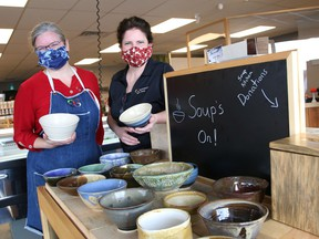 """Owners Rachelle Rocha, left, and Laurie Pennell, of Seasons Pharmacy and Culinaria, display bowls created by the Sudbury Basin Potters at their business on Lorne Street in Sudbury, Ont. on Friday November 20, 2020. """"Soup's On Reimagined"""" - Lunch with Sudbury Basin Potters for the Blue Door Soup Kitchen, will be held every day from Nov. 20-30 at Seasons Pharmacy and Culinaria, except on Sundays. All bowls will be priced at $12, with all money raised donated to the Blue Door Soup Kitchen."""