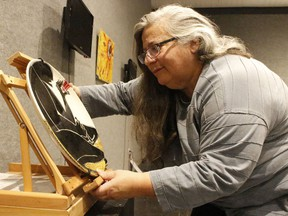 Lise B. L. Goulet, curator of the travelling exhibit named Crossroads, was setting up an art piece by artist Paul Walty at the Timmins Museum on Monday. It is among the pieces being showcased during the museum's new exhibition which runs from Nov. 10 to Dec. 4.   RICHA BHOSALE/The Daily Press