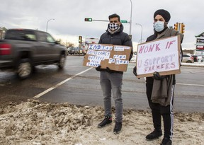 Jashan Brar (left) and Harsahay Singh  hold up protest signs at the intersection of 108 Street and 100 Ave Tuesday, Dec. 1, 2020, in solidarity with Indian farmers. The pair, along with two others on the east side of 108 Street, wanted to show that Indian farmers have support across the world.