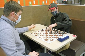 Evan Kilroy makes a chess move while Adam Wallace watches. The North Bay Chess Club is continuing to meet and play games, although members admit more games are being played online due to the COVID-19 pandemic. PJ Wilson/The Nugget