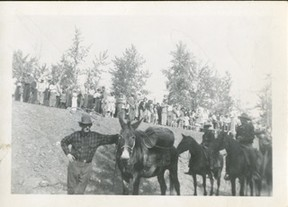 PRMA 1978.932.018 – Information associated with this photograph of Baldy Red (George Yeoman) and his unnamed mule (note what appears to be a keg strapped to its side) and many other celebrants, suggests it was taken at the time of the opening of the (old) Smoky River Bridge southeast of Tangent in 1949/50, since replaced. On further investigation, the timing of the bridge completion and Baldy's and mule's attendance is not possible, as Baldy, according to two divergent sources died, in either 1936 or 1943.