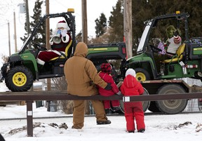Santa Claus and the Grinch wave to residents of Josephburg during a Santa Convoy through rural Strathcona County on Sunday Dec. 20. David Bloom/Postmedia