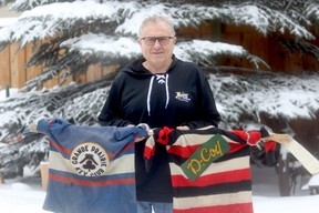 Grande Prairie Hockey Legends chairman Stan Neufeld holds two jersey's from the legends memorabilia collection. The hockey history group is in fundraising mode, trying to raise money for a new display case.  The blue sweater is from the Grande Prairie Key Club, circa 1947 and the striped sweater is the Grande Prairie DCoy, circa 1947-48..