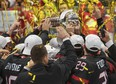 Team Canada players reach for the trophy after defeating Russia 4-3 in the gold medal game earlier this year.