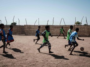 Ethiopian refugees who fled the Tigray conflict, play football in a playground set by Save the Children at Um Raquba reception camp in Sudan's eastern Gedaref province on December 3, 2020. - More than 45,000 people have escaped from northern Ethiopia since November 4, after Prime Minister Abiy Ahmed ordered military operations against leaders of Tigray's ruling party in response to its alleged attacks on federal army camps. (Photo by Yasuyoshi CHIBA / AFP)