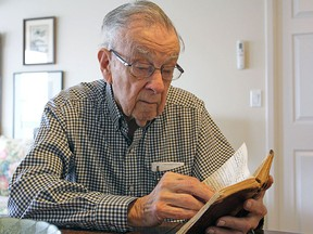 Bill Fitsell, at his home in Kingston in April 2017, reads the diary he wrote while serving in the Royal Canadian Navy during the Second World War.