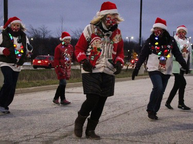 Members with the Sarnia Outta-Liners Line Dance Group perform as one of the entries in the drive-thru Santa Claus Parade at  Lambton College Dec. 5 in Sarnia. There was bumper-to-bumper traffic over three hours to see stationary displays in this year's modified parade event, organizers with the Sarnia Kinsmen Club said. (Tyler Kula/The Observer)