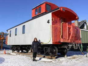 Monica Towsley, program coordinator with the Timmins Museum, stands next to the museum's newest outdoor exhibit: An old T&NO railway caboose. Like the old Hollinger House that it has been placed next to, it will be opened to the public at some point and people will be able to tour through it.  RICHA BHOSALE/The Daily Press