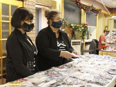 Holly Morissette, left, was helping out her friend and owner of the Mask Persona, Heather Ferguson,while serving customers at their booth at the holiday pop-up shop on Saturday.  RICHA BHOSALE/The Daily Press