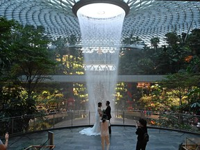 Newlyweds pose for their photographer against the rain vortex at Changi Jewel in Singapore. ROSLAN RAHMAN/AFP via Getty Images)