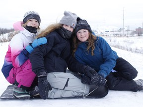 The sliding hill just off Highway 655 at the end of Ross Avenue is always a popular draw during the Christmas/New Year's holiday break. Among those out tobogganing on Monday were, from left, Kylie Pineault, Emelie Chartrand and Danielle Belanger.  RICHA BHOSALE/The Daily Press