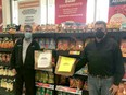 Butch Dionne presents Claude Rocheleau with a couple from the 1000 bags that were given to the Food Bank by patrons of Dionne's valu-mart.TP.jpg