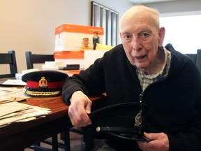 Bill Hackett with his numerous newspaper clippings, badges, notes and old police hats on May 3, 2019.