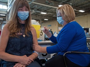 Theresa Burns, a long-term care worker at Greenwood Court, receives a COVID-19 vaccination from Debbie Karz, a public health nurse with the Middlesex-London Health Unit.  CHRIS MONTANINI\STRATFORD BEACON HERALD