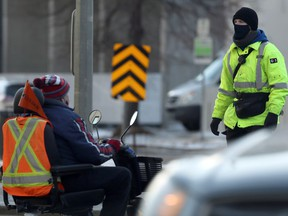 A G4S security guard member (right) crosses Memorial Boulevard in Winnipeg on Thurs., Nov. 26, 2020. The firm was hired to help enforce health orders. Kevin King/Winnipeg Sun/Postmedia Network