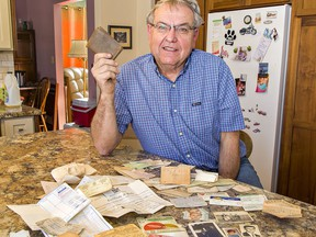 Ken Mercer of Cainsville shows his father's wallet -- and its myriad of contents -- that was lost 47 years ago in Hamilton, and returned after a contractor discovered it behind bricks in the basement of a Hamilton home under renovation.
