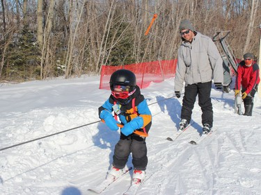 Jacob Rose makes his way up the hill, with dad Martin Rose not far behind, and Big Ben volunteer Ron Lauzon at the tow lift controls. Photo on Sunday, February 21, 2021, in Cornwall, Ont. Todd Hambleton/Cornwall Standard-Freeholder/Postmedia Network