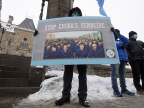 Protesters gather outside the Parliament buildings in Ottawa on Monday, Feb. 22. Parliament overwhelmingly supported an opposition motion calling on Canada to recognize China's actions against ethnic Muslim Uighurs as genocide.
