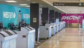 Empty lines of check-in desks for Air Canada, WestJet and Swoop at London International Airport. (Mike Hensen/The London Free Press)