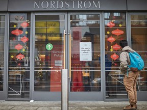 A man stands in front of the Nordstrom store, closed for in-store shopping in downtown Toronto, on Nov. 23, 2020.