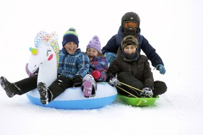 The smiles and giggles were obvious as Miles Linton (left), 8; his sister Grace, 6; Matteo Valentino, 11 and brother Marco (in helmet), 8, all of Mitchell soar down the Mitchell Lions Pool hill on Jan. 29. They weren't the only ones enjoying the outdoor fun, as the hill proved a popular place all weekend.  ANDY BADER/MITCHELL ADVOCATE