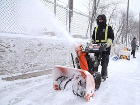 City employee Tyler Brady uses a snowblower to clear snow off the rink at Elm West Playground in Sudbury, Ont. on Friday February 5, 2021. John Lappa/Sudbury Star/Postmedia Network