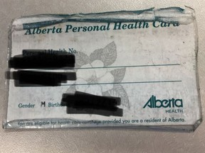 An Alberta Personal Health Card in its natural state: Frayed, battered and suffering from an ad hoc lamination attempt.