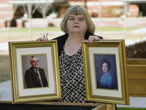 Lynda Stewart holds a photo of her father Lowell Stewart and her mother Jean Stewart outside her home in Sherwood Park, on Friday, March 19. Both of her parents died from COVID-19. Lynda also contracted the coronavirus and almost died but has since recovered. LARRY WONG/Postmedia