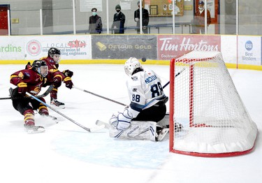 Timmins Rock captain Derek Seguin, left, and blue-liner Evan Beaudry apply the brakes as the puck sails over the shoulder of Crunch goalie Michael Nickolau but over the crossbar, as well, during Wednesday night's NOJHL game at the Tim Horton Event Centre in Cochrane. The Rock went on to defeat the Crunch 5-2 for their sixth victory in seven tries against the East Division rivals this season. The two sides will play their eighth game at the McIntyre Arena on Thursday, at 8:30 p.m. THOMAS PERRY/THE DAILY PRESS
