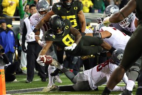 Jevon Holland of the Oregon Ducks dives for a 19-yard pick six against the Washington State Cougars.