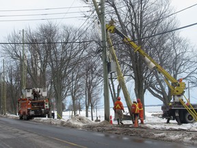 Utilities Kingston workers install new poles along King Street.