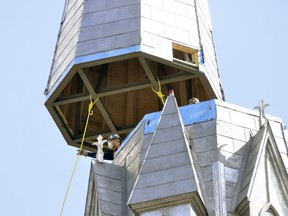 On-site workers guide a 40-foot piece, complete with a seven-foot cross, on the steeple of St. Patrick's Church in Kinkora March 24. It's been 17 1/2 years since the steeple has been in place, a landmark for miles around that parishioners say makes the Catholic church complete once again. (ANDY BADER, Postmedia Network)