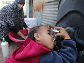 A Palestinian child drinks water from a public tap in the southern Gaza Strip on March 21, 2021.