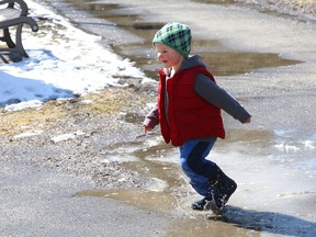 Two-year-old Nolan Sarazin has fun splashing in ice-covered puddles at Bell Park in Sudbury, Ont. on Monday March 29, 2021. John Lappa/Sudbury Star/Postmedia Network
