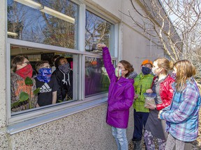 Rachel Brown adds birdseed to the window feeder at Port Rowan Elementary School on March 8. he Long Point Biosphere Reserve has provided FeederWatch kits to 50 classrooms in Haldimand and Norfolk counties. Classmates with her outside are Josh Hunt, Joelle Plumley and Avery Block (right). Brian Thompson/Postmedia Network