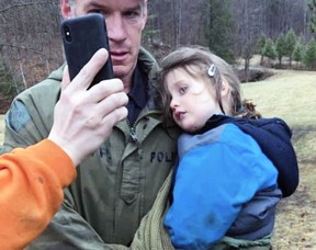 Ontario Provincial Police Const. Scott McNames carries Jude Leyton, 3, back to his family in South Frontenac while FaceTiming his parents on Wednesday. Jude had been missing in the thick forest for three and a half days.