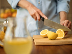 Pitcher with lemonade and woman cutting lemons