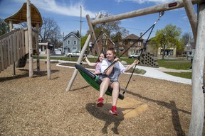 Lennon Jackson, 6, left, and her cousin Adelle LeBlanc, 15, enjoy the big swing on opening day of Lorne Avenue Park in London on Wednesday April 28, 2021. The park is on the site of the former Lorne Avenue public school in Old East London. (Derek Ruttan/The London Free Press)