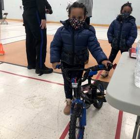 Melat, 4, stands with a bicycle she received at a recent event which provided free bikes and training on cycling and street safety in Owen Sound to newcomers. Her sister, Arsama, 6, is behind her. (Supplied photo)