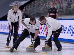 Team RCF skip Sergey Glukhov (left) follows his sweepers during his team's Draw 17 win over Canada at the world men's curling championship in Calgary.
