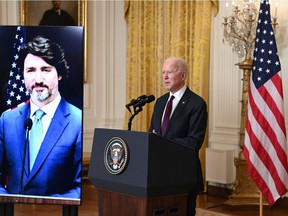 Prime Minister Justin Trudeau appears on- screen as U.S. President Joe Biden speaks to the media in February after the two held a virtual bilateral meeting. The Americans have hit their stride in battling COVID-19; Canada's approach lacks focus and coherence.