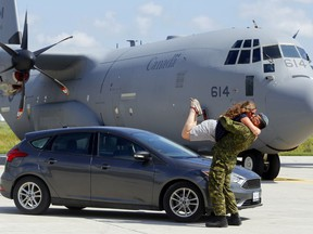 Sarah Heino takes to the air while kissing her husband, Cpl. Julian Tutino, Aug. 26 at the first Rubber on the Ramp United Way fundraiser at CFB Trenton. It allowed citizens to be photographed with their vehicles next to military aircraft - in this case a CC-130 Hercules transport. It garnered photographer Luke Hendry a mention as a finalist in the 2020 Ontario Newspaper Awards, announced Friday, for feature photography in newspapers with circulations of less than 25,000.
