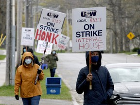Trudy Arthur, left, and Heidi Hatch join fellow Interval House workers in a small picket on Park Street on April 27. The workers have reached a deal with management. (FILE PHOTO)