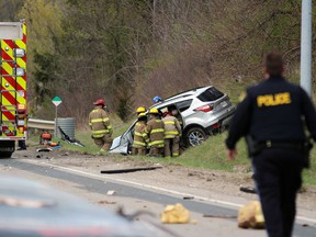 Firefighters extricate two people from an SUV after it crashed into a trailer pulling a boat on Oil Heritage Road near Discovery Line on Friday April 23, 2021 in Petrolia, Ont.