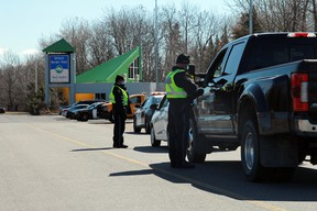 Kenora OPP officers question motorists entering Ontario at the rest stop at the provinical border with Manitoba on Monday, April 19. The Ontario government has placed restrictions on inter-provincial travel amid rising COVID-19 cases.
