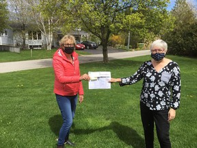 For the fourth year in a row, Tiverton's Shelly Parker (left) is the top fundraiser in the Huron Shores Hospice virtual hike from home May 8. She presented a $6,164 cheque and ledge sheets to to hospice board co-chair Cheryl Cottrill. SUBMITTED