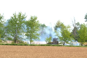 Stratford and Perth East firefighters responded to a grass fire in a farmer's field at the west end of Stratford Sunday night. Pictured, smoke could still be seen billowing from the field Monday morning. Galen Simmons/The Beacon Herald/Postmedia Network