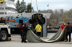 Men wait with a tarp to cover a van which was pulled out of the harbour Sunday afternoon in Owen Sound as part of a sudden death police investigation. (Scott Dunn/The Sun Times/Postmedia Network)